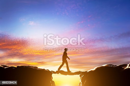 Man walking over precipice between two mountains, another man serving as a bridge. Sunset, business conceptual