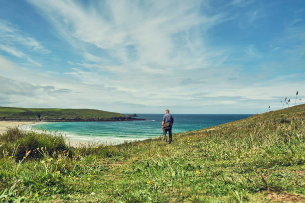 man walking the coastpath at pentire, newquay overlooking crantock beach on a bright sunny june day. - cornwall stock pictures, royalty-free photos & images