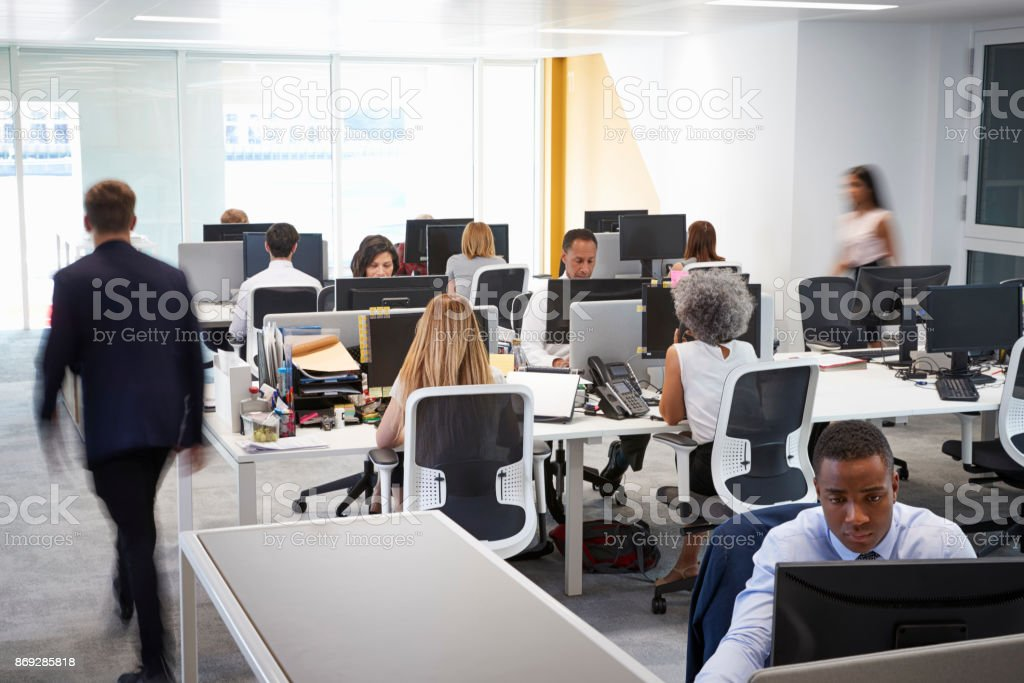 Man walking through a busy open plan office stock photo