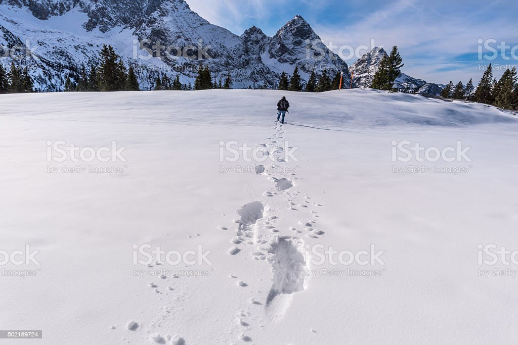 Man walking through snow on a mountain peak stock photo