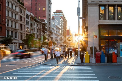 813211754 istock photo Man walking through the crosswalk at the busy intersection of 5th Avenue and 23rd Street in New York City 1173235188