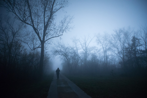 Man walking through the misty forest at winter night