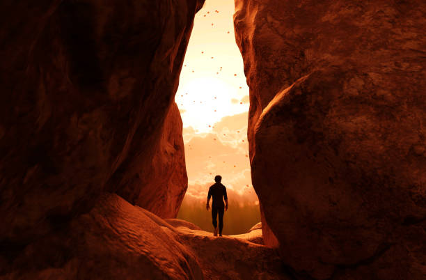 Man walking to the light and exit the cave Man walking to the light and exit the cave,3d illustration adventure stock pictures, royalty-free photos & images