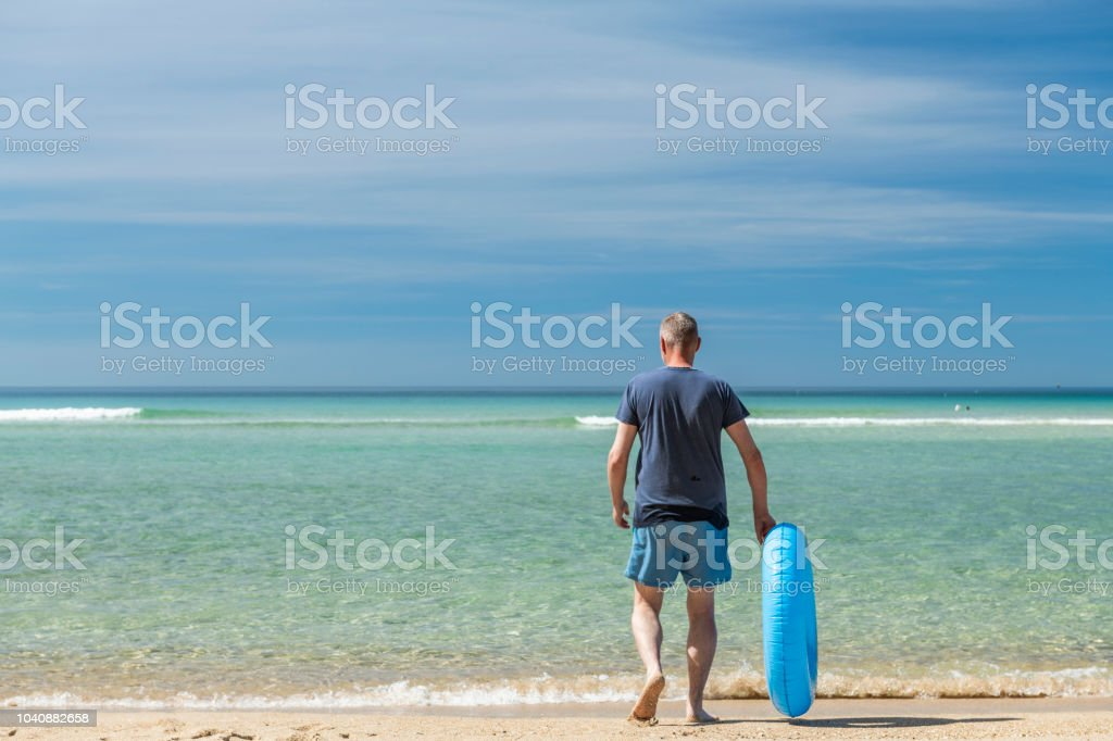 Man walking to the sea with rubber ring, Pedn Vounder Beach, Cornwall stock photo