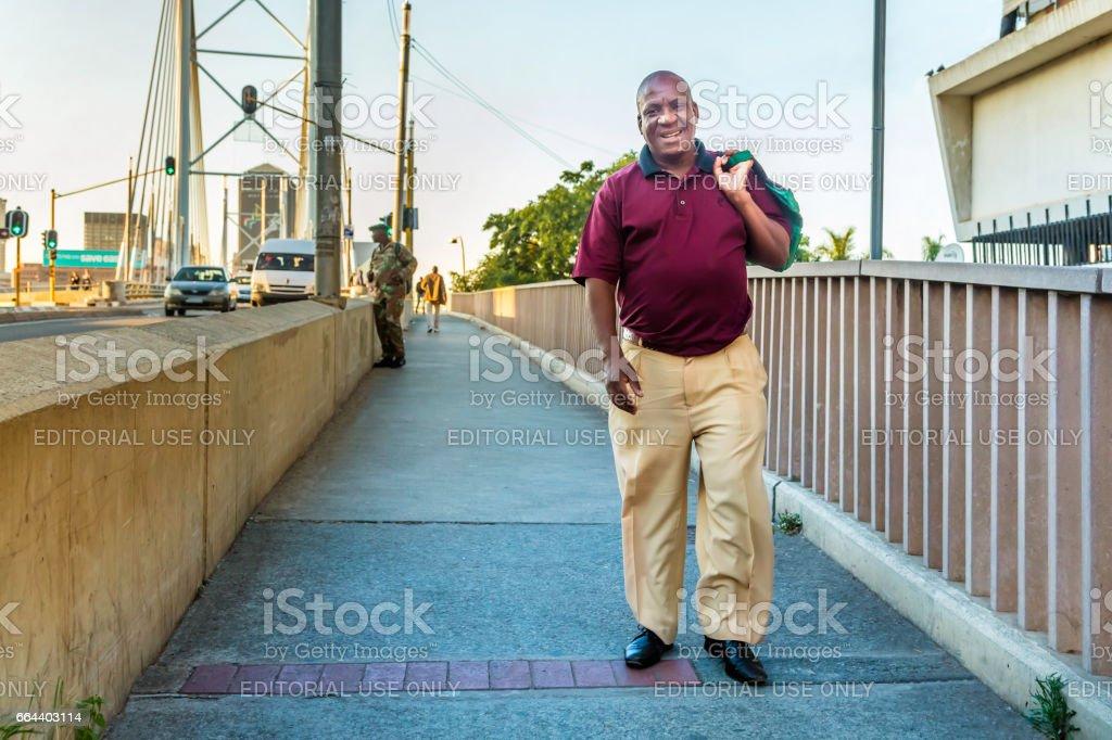 Man walking to work over Nelson Mandela bridge stock photo