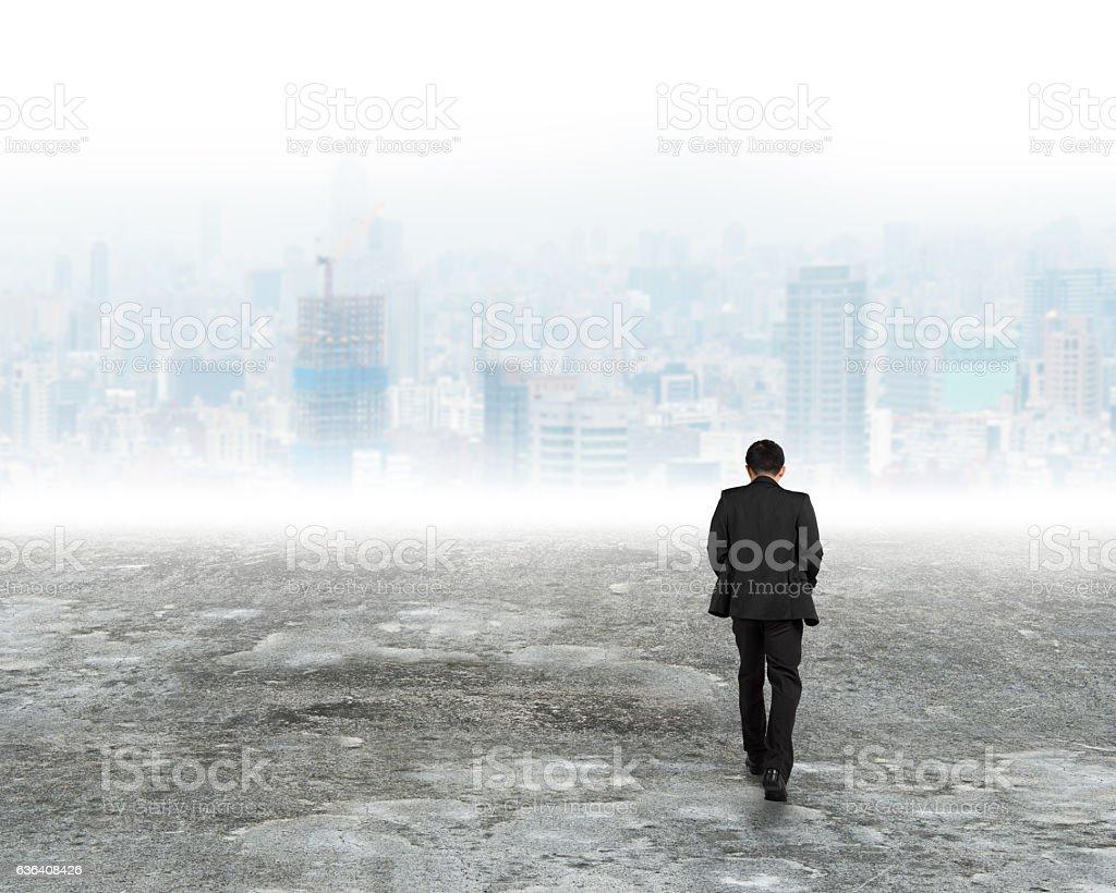 Man walking toward city buildings in mist stock photo