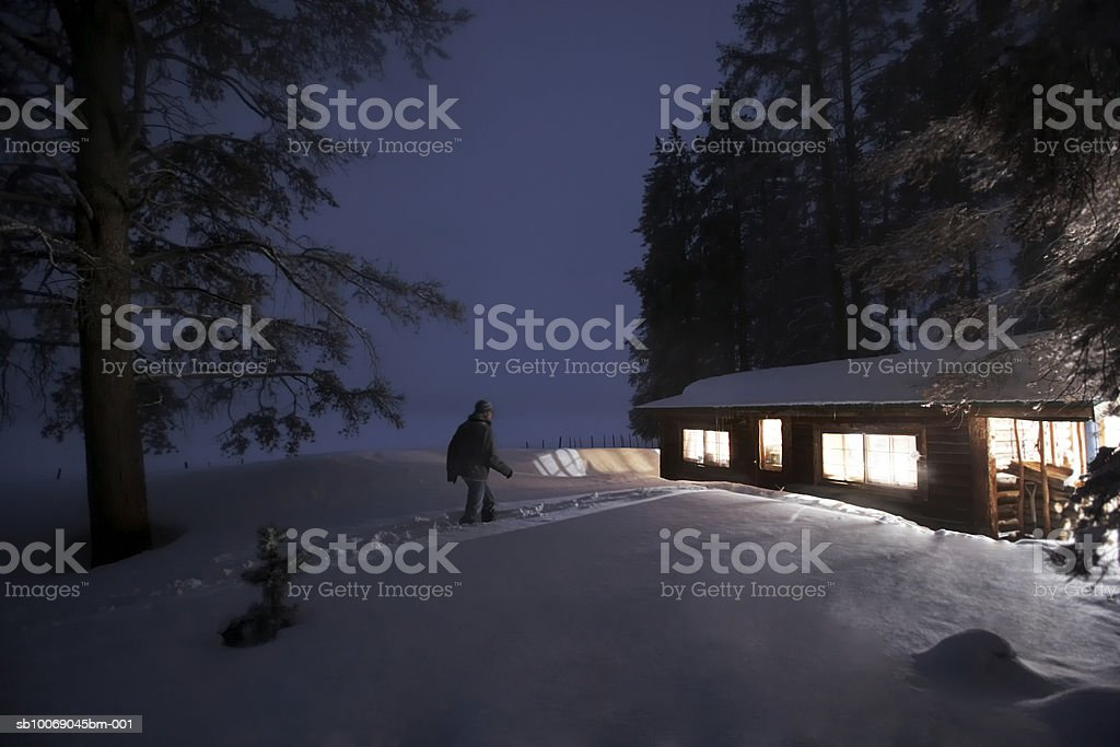 Man walking towards house in snow royalty-free stock photo