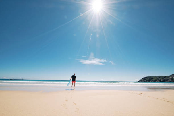 man walking towards the waters edge of the pristine pedn vounder beach, cornwall on a hot sunny june day. - rubber ring stock photos and pictures