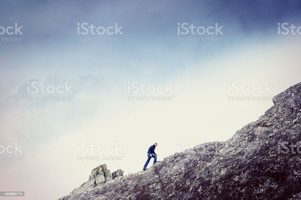 Man walking up a steep rock face stock photo