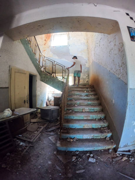 Man walking up an abandoned staircase stock photo