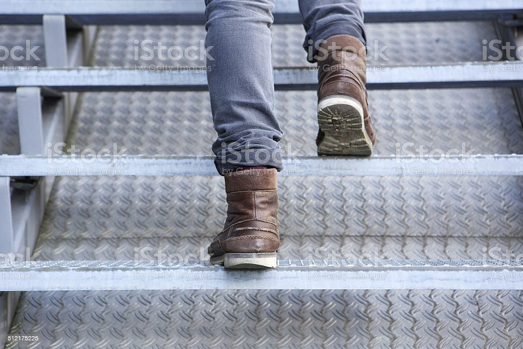 Man walking up stairs in boots stock photo