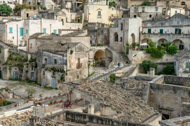 Man walking up stairway in Matera, Basilicata, Italy Stairways and doorways of old town of  Matera, Basilicata, Italy matera italy stock pictures, royalty-free photos & images