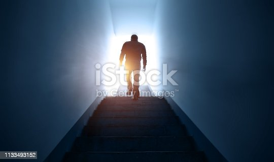 Man walking upstairs into the light.