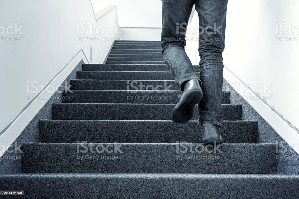 Man walking upstairs stock photo