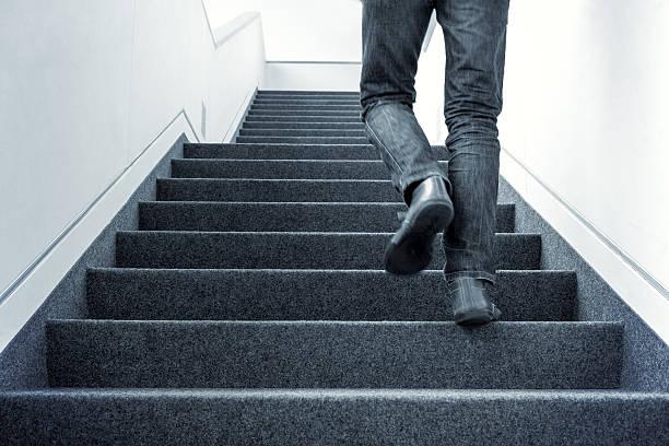 Man walking upstairs stock photo