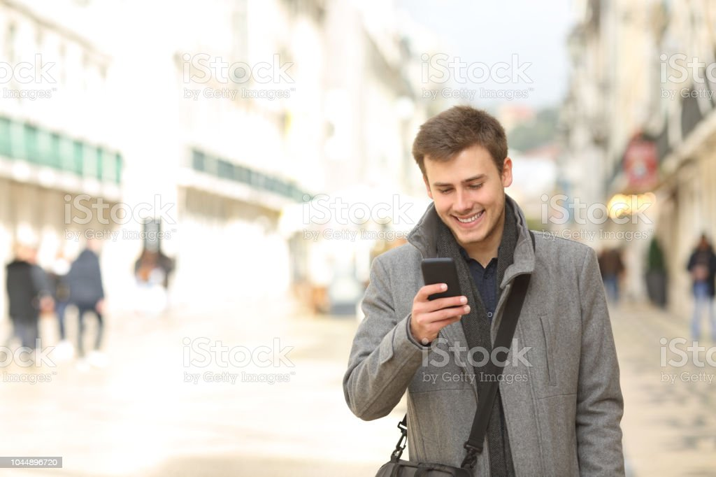 Man walking using a smart phone in winter in the street stock photo