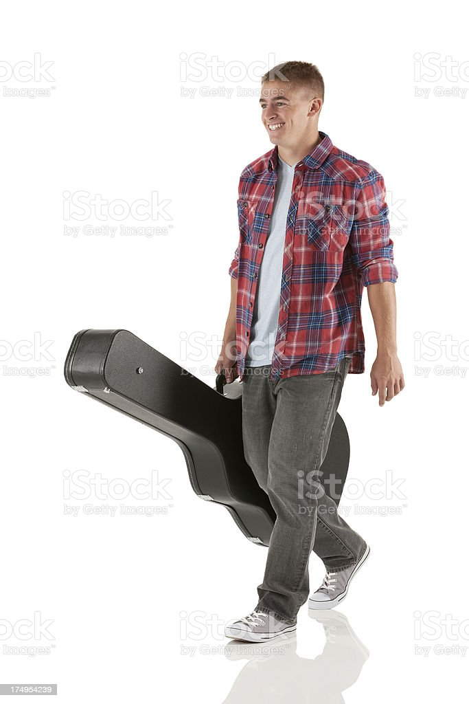 Man walking with a guitar case royalty-free stock photo