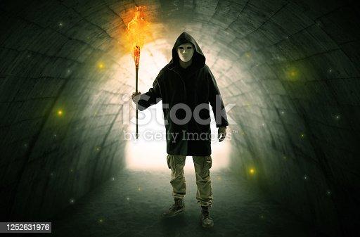istock Man walking with burning flambeau in a dark tunnel 1252631976