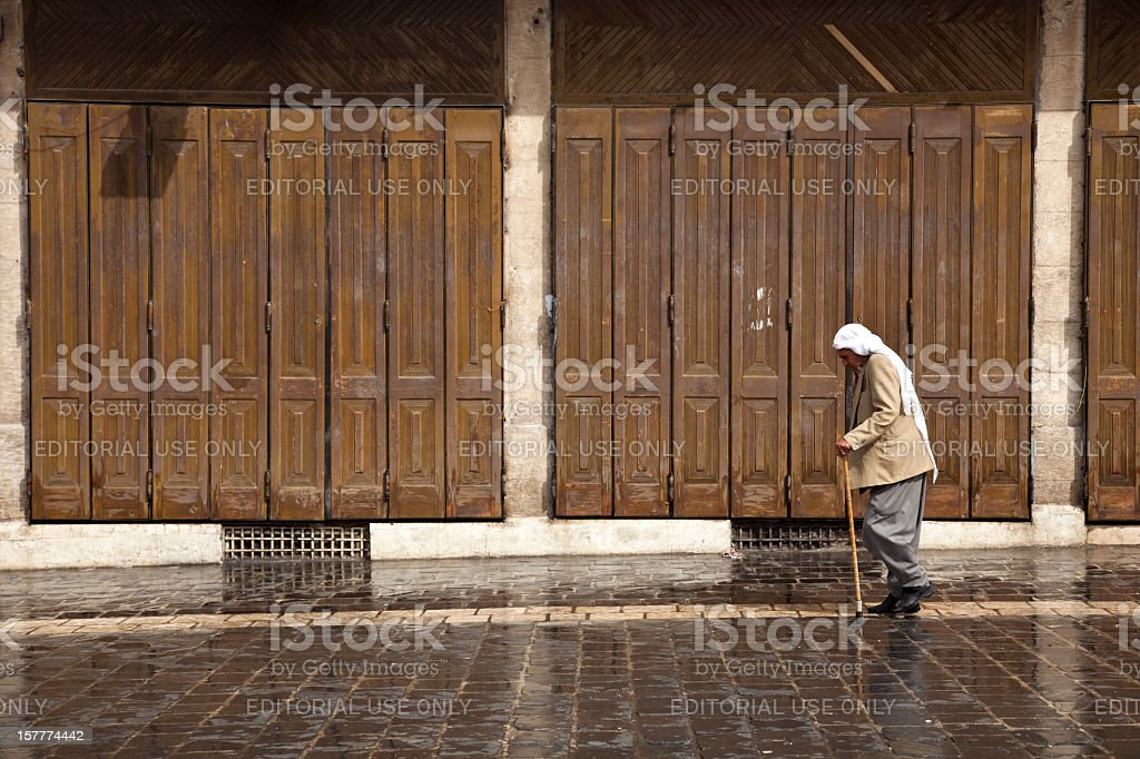 Man walking with cane in the street of Aleppo. stock photo