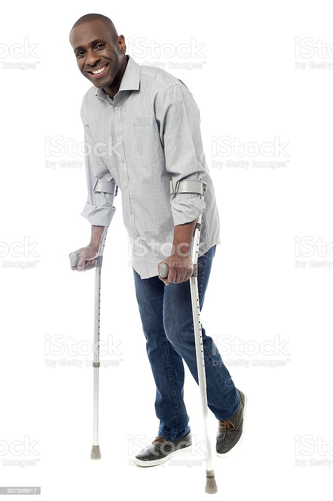 Man walking with crutches isolated on a white Smiling man with crutches trying to walk Adults Only Stock Photo