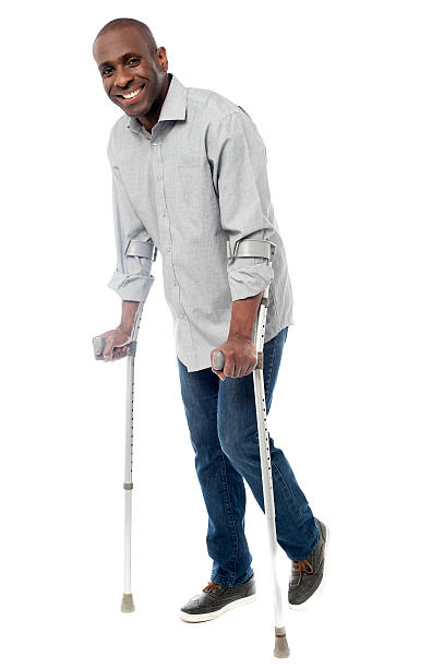 Man walking with crutches isolated on a white stock photo