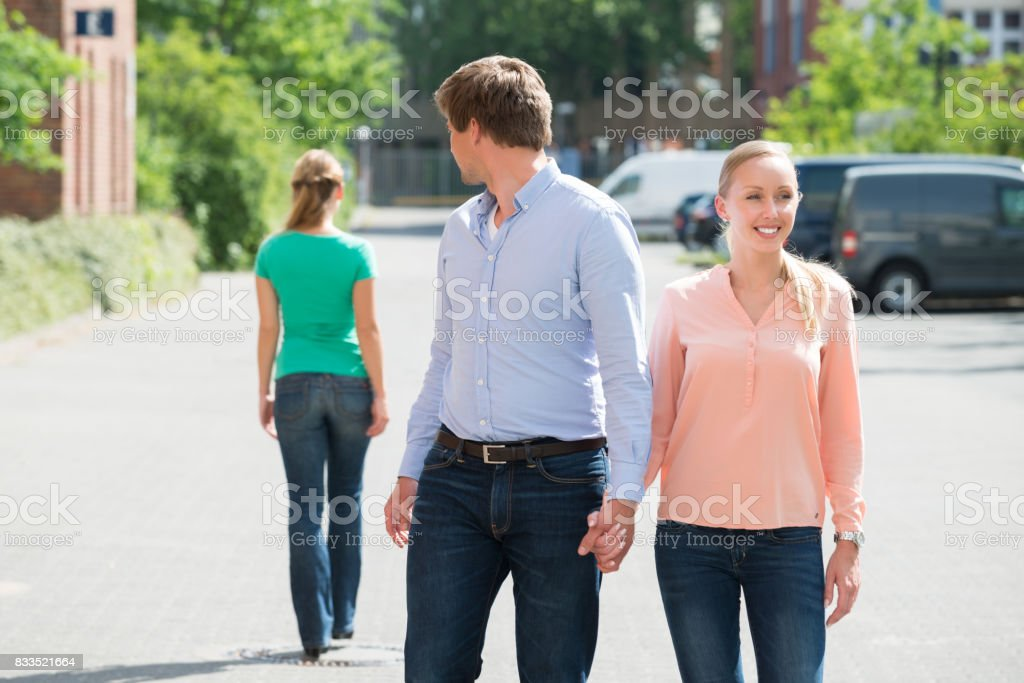 Man Walking With His Girlfriend Looking At Another Woman stock photo