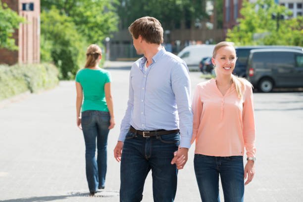 Man Walking With His Girlfriend Looking At Another Woman Young Man Walking With His Girlfriend On Street Looking At Another Woman former stock pictures, royalty-free photos & images