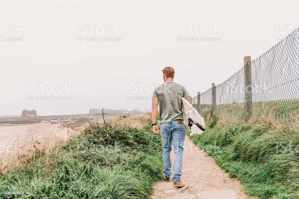 Man walking with his surfboard above Fistral Beach, Newquay, Cornwall on an Autumn day. stock photo
