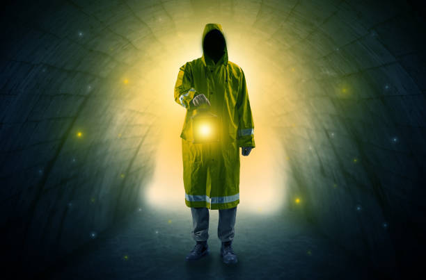 Man walking with lantern in a dark tunnel Ugly man in raincoat walking with glowing lantern in a dark tunnel bootes stock pictures, royalty-free photos & images