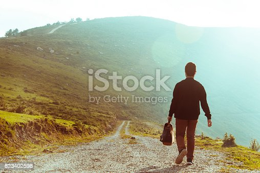 A rear view of a young man holding a suitcase, walking in a mountain area.