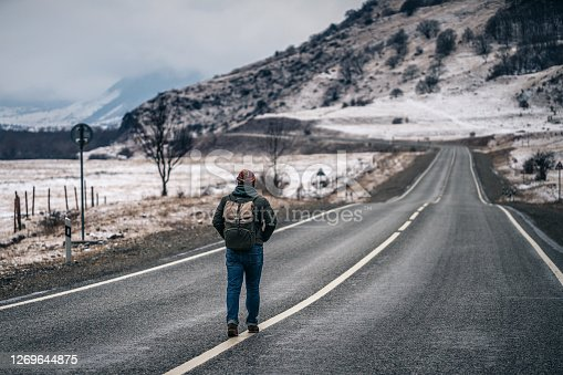 Man walks alone on an empty road in mountains.
