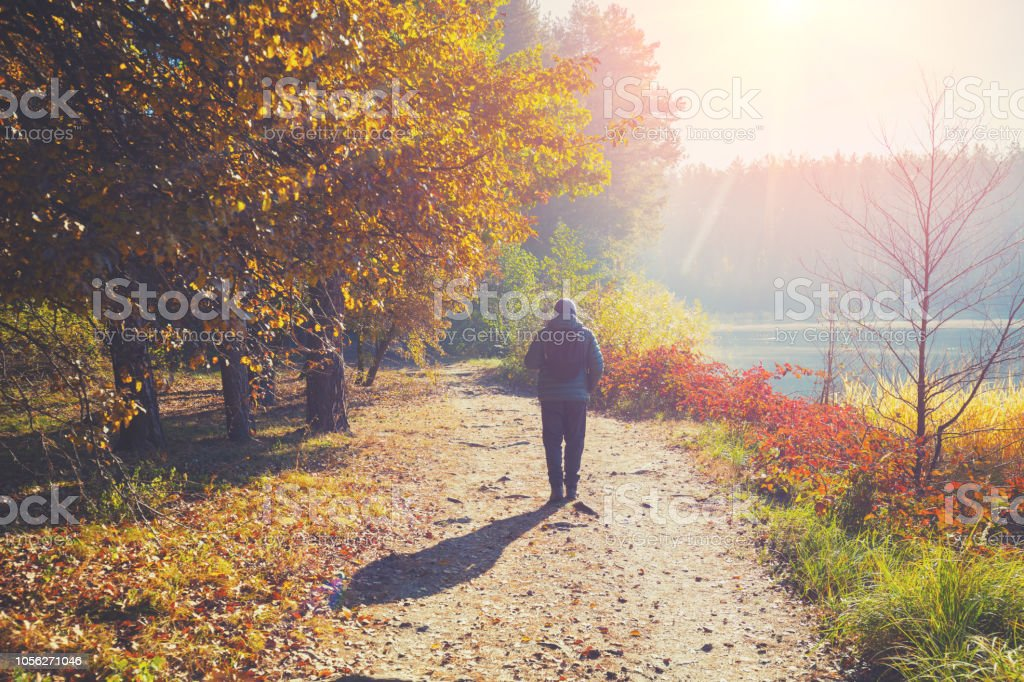 Ein Mann geht auf einem Weg in einem Park in der Nähe von einem See in den frühen Morgenstunden im Herbst – Foto