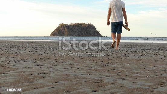istock Man walks along beach at sunrise 1214508233