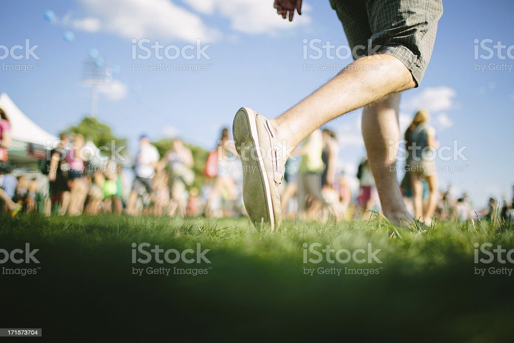 Man walks in front of crowd at music festival stock photo