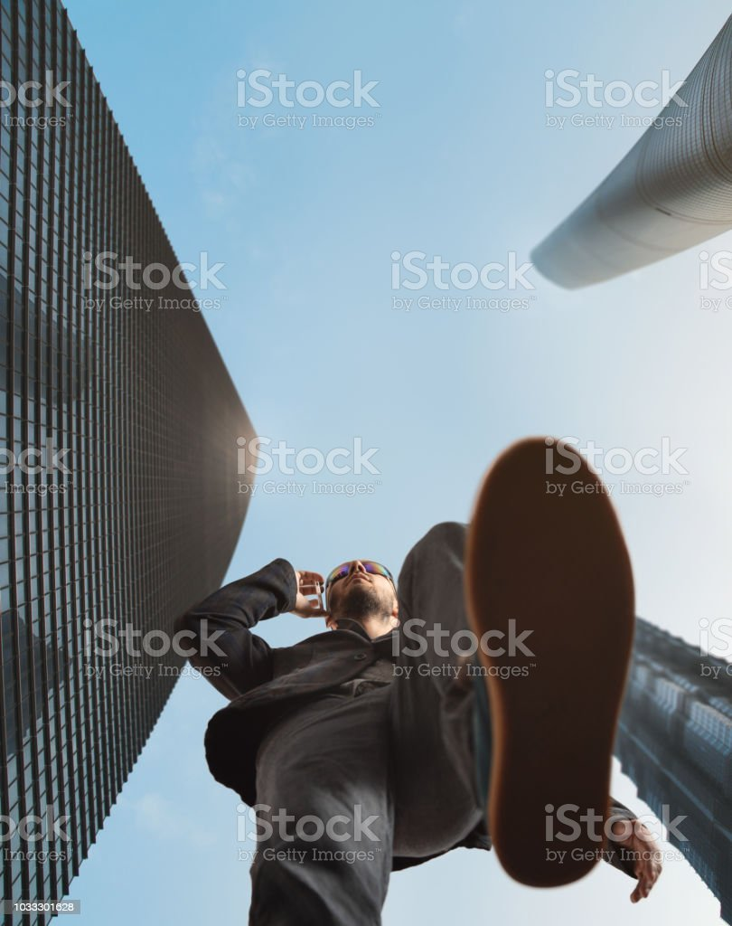 A man walks into the city and talks on his cell phone. Bottom view