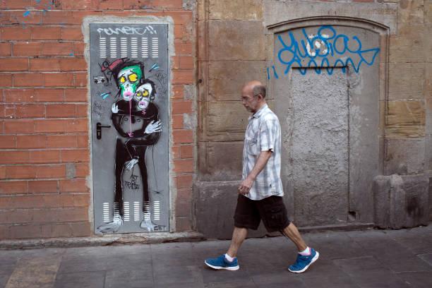 mann geht neben einer hauswand mit einem lustigen malerei in spanien - schlechte laune sprüche stock-fotos und bilder