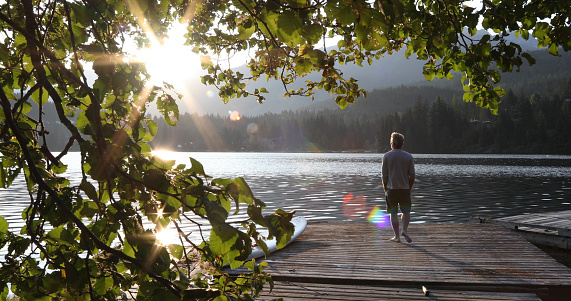 Man walks onto dock over lake and watches sunrise over mountains and forest