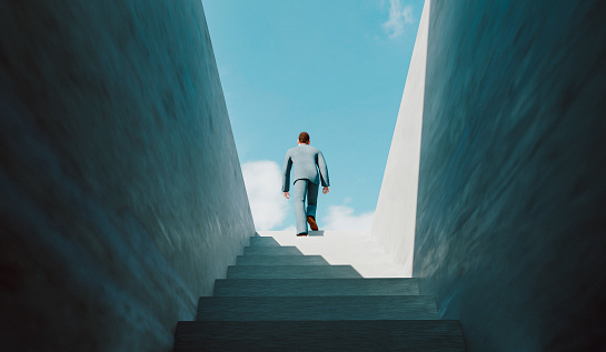 Concept of taking the right decisions and be moving in the right direction. Businessman walks on a staircase from a dark cellar to the top where he reaches sunshine and success. Note: The man is a 3D-render with face scan. Model release attached.