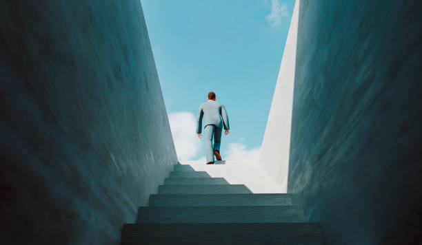 Man walks the ladder of success and reaches the top stock photo