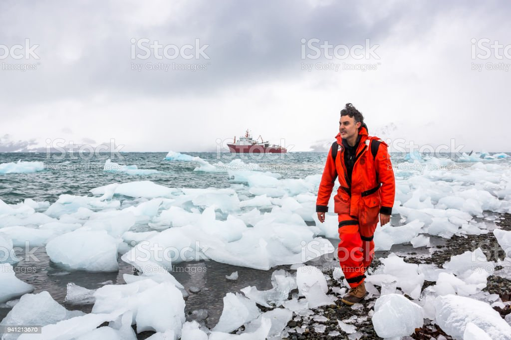 Man walks through ice and snow in Antarctica. Icebergs and everything frozen around you. stock photo