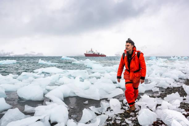 Hombre camina a través del hielo y la nieve en la Antártida. Icebergs y todo congelado a tu alrededor. - foto de stock