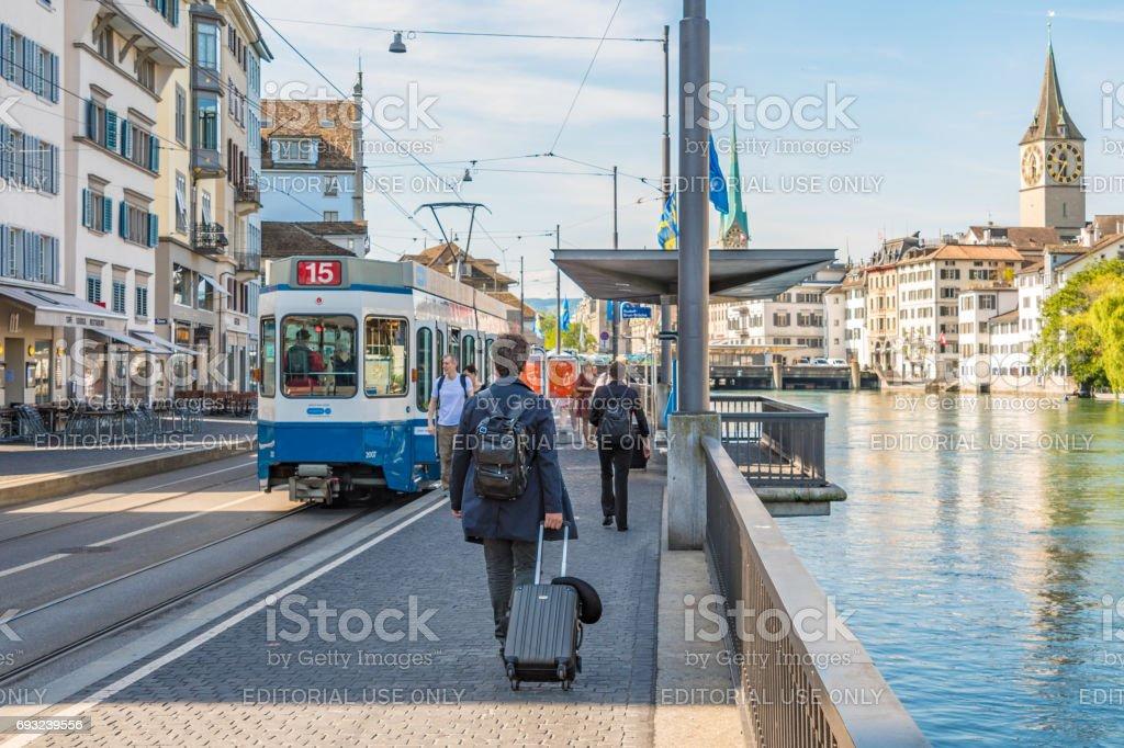 Man walks with suitcase towards tram in Zurich stock photo