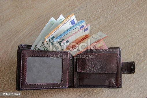 Man wallet with euro money lies on the table. Many euros look out of the pocket of the wallet that lies on the table.
