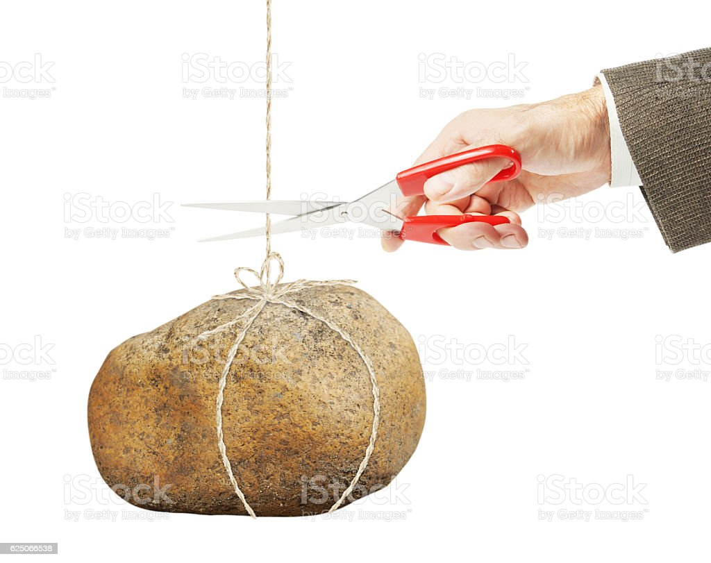 Man wants to cut rope on which hangs large stone stock photo