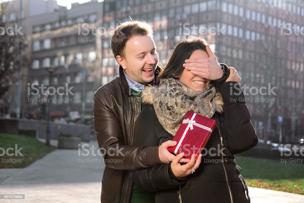 Man wants to surprise the girl with a gift stock photo