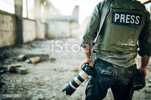 One man, war journalist with digital camera at the place of action, in war zone.