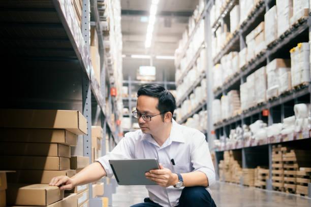man magazijnmedewerker controleren van goederen in het magazijn. - warehouse worker stockfoto's en -beelden