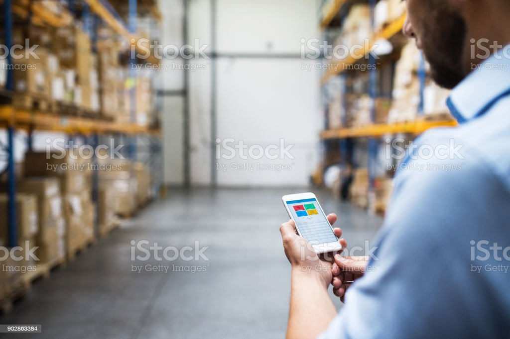 Man warehouse worker with a smartphone. stock photo