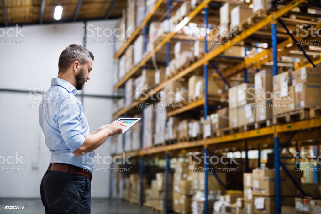Man warehouse worker with a tablet. stock photo