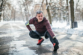 One man, senior adult guy preparing for jogging outdoors in park, on a cold winter day alone.